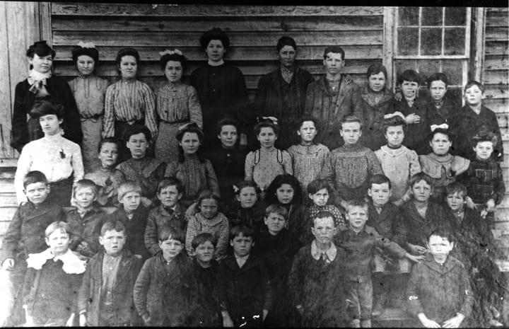 Oak School Taught by Minnie Coogler: st row: 1. Sam Jones, 2. Frank Terrell,</br> 3. David (Buddy) Pope, 4. Jim B. Beasley, 5. Eugene Reeves, 6. Unknown, 7. George Moody, 8. B. D. Stephens, 9. Duard Terrell.</br> 2nd row: 1. Vera Stephens, 2. Ruben Baker, 3. Clifford Kidd, 4. Dan Ed Humphries, 5. Tela Holland, 6. </br>Sallie Ree Humphries, 7. Essie Reeves, 8. Maud Kidd, 9. Carl Terrell, 10. Glenn McNair, 11. Allen McNair. 3rd row: 1. Miss Minnie Coogler </br>(teacher); 2. Florence Stephens; 3. Della Reeves; 4. Ethel McNair; 5. Blanch Stephens; 6. Mollie Kidd; 7. Buela Holland.</br> 4th row: 1. Clyde McNair; 2. Mary Jones; 3. Mattie McNair; 4. Annie Terrell; 5. Eunice Reeves; 6. William McNair; 7. Raymnd Terrell; 8. Lorrell Terrell; </br>9. Irby Terrell; 10. Amos Baker; 11. Howard Pope.
